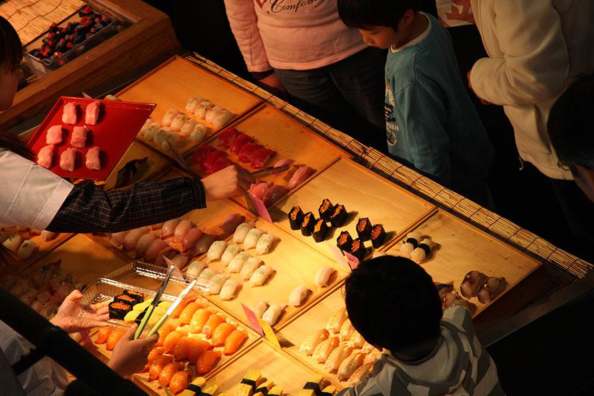 Para pembeli yang sedang memilih hidangan sushi di kedai di Karato Market